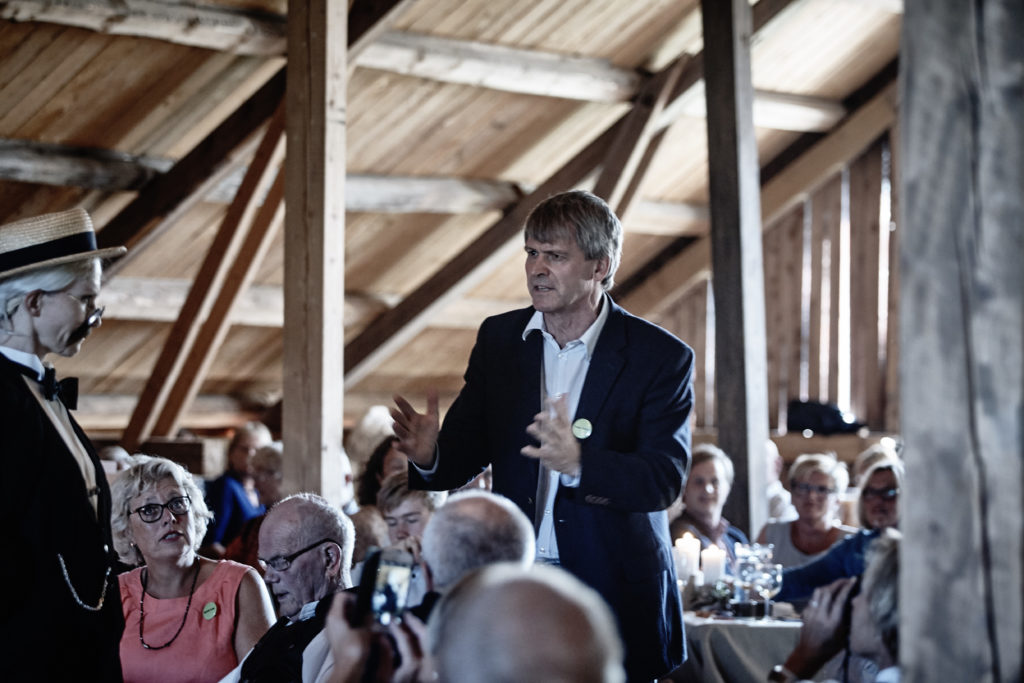 The dialogue between Professor Birkeland and Mr. Ingels starts amidst lunch guests in the barn at Strand gard in Norway